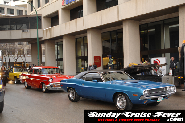 '57 chevy and 1970 Plymouth Cuda pulling out of the 2009 Winnipeg World of Wheels